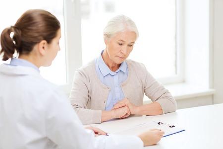 ヘルスケア: 医学、年齢、医療、人々 コンセプト - 病院待ち合わせクリップボード、シニアの女性と医師 写真素材