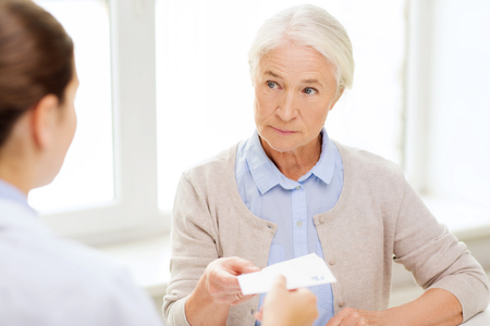 health care and medicine: medicine, age, health care and people concept - doctor giving prescription to senior woman at hospital Stock Photo