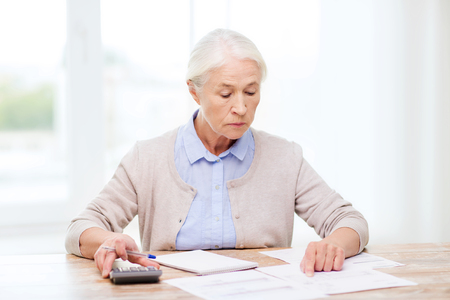business savings: business, savings, annuity insurance, age and people concept - senior woman with papers or bills and calculator writing at home