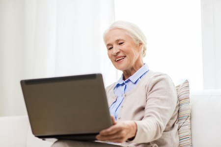 computer age: technology, age and people concept - happy senior woman with laptop computer at home