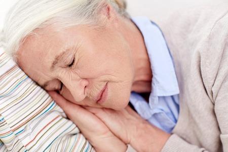 gente durmiendo: edad, relax y la gente concepto - mujer mayor feliz durmiendo en la almohada en casa