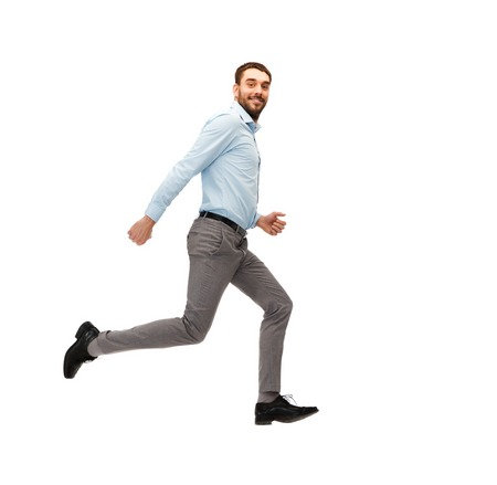 isolated man: business, freedom, movement and people concept - smiling young man jumping or running away Stock Photo