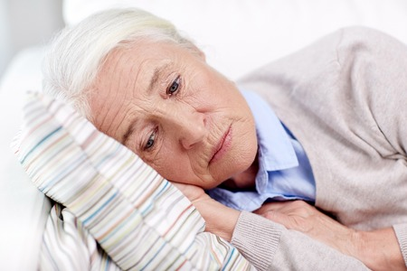 age, sadness, trouble, problem and people concept - sad senior woman sleeping on pillow at home Standard-Bild