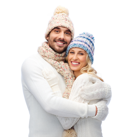 fleece: winter, love, couple, christmas and people concept - smiling man and woman in hats and scarf hugging