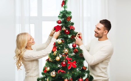 decorating: family, x-mas, winter holidays and people concept - happy couple decorating christmas tree at home