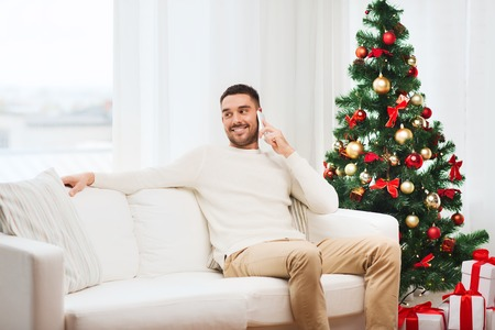 call: christmas, technology, people and holidays concept - smiling man calling on smartphone at home