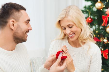 verlobung: liebe, weihnachten, paare, Vorschlag und Menschen Konzept - gl�cklicher Mann Diamant-Verlobungsring in kleinen roten Feld auf Frau zu Hause zu geben