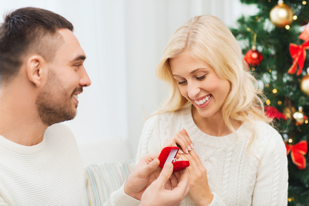 proposing: love, christmas, couple, proposal and people concept - happy man giving diamond engagement ring in little red box to woman at home Stock Photo