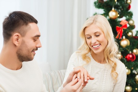 happy christmas: love, christmas, couple, proposal and people concept - happy man giving diamond engagement ring to woman at home