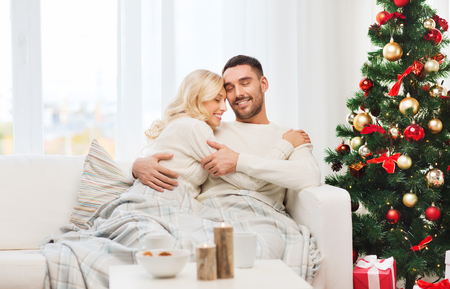 couple cuddling: family, christmas, holidays, love and people concept - happy couple covered with plaid sitting on sofa at home