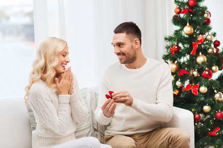 proposing: love, christmas, couple, proposal and people concept - happy man giving engagement ring in little red box to woman at home