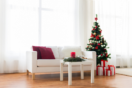 red sofa: holidays, celebration, decoration and interior concept - sofa, table and christmas tree with gifts at home