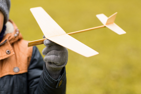 model airplane: autumn, childhood, dream, leisure and people concept - close up of little boy hand holding toy plane outdoors