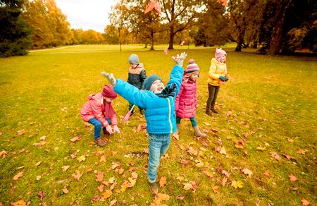 leisure: childhood, leisure, friendship and people concept - group of happy kids playing with autumn maple leaves and having fun in park