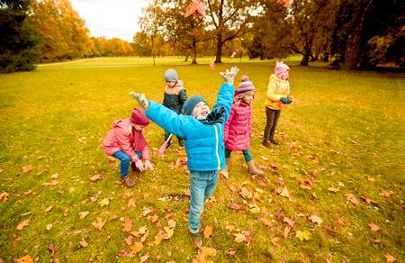 infancia: la infancia, el ocio, la amistad y el concepto de la gente - grupo de niños felices jugando con las hojas de arce del otoño y que se divierten en el parque Foto de archivo