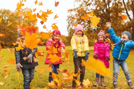 happy kids: childhood, leisure, friendship and people concept - group of happy kids playing with autumn maple leaves and having fun in park