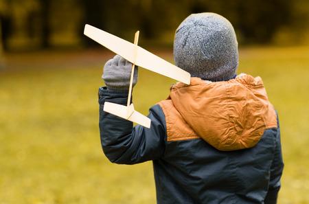 ni�o modelo: oto�o, la infancia, el sue�o, el ocio y el concepto de la gente - ni�o feliz jugando con avi�n de juguete de madera al aire libre de la parte posterior