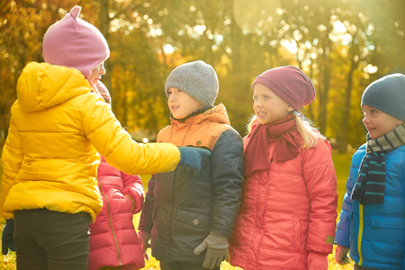 choosing: childhood, leisure, friendship and people concept - group of happy kids in autumn park counting and choosing game leader Stock Photo