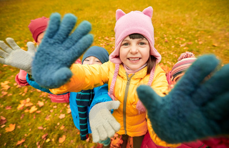 kids hand: childhood, leisure, friendship and people concept - group of happy children waving hands in autumn park Stock Photo