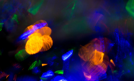 bokeh lights: holidays, illumination and electricity concept - colorful bright night lights bokeh over dark background Stock Photo