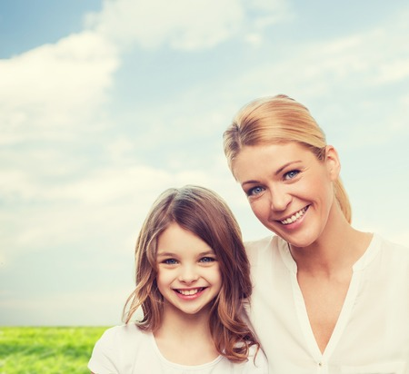 happy teenagers: family, childhood, happiness and people - smiling mother and little girl over blue sky and grass background