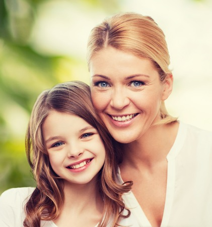 preteen: family, childhood, happiness, ecology and people - smiling mother and little girl over green background