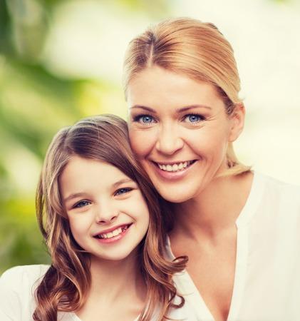 madre e hija adolescente: la familia, la infancia, la felicidad, la ecología y personas - madre sonriente y niña sobre fondo verde