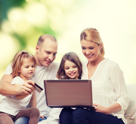 green technology: family, shopping, technology and people - happy family with laptop computer and credit card over green background Stock Photo
