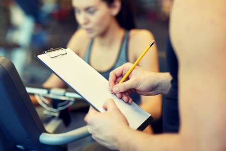 fitness trainer: sport, fitness, lifestyle, technology and people concept - close up of trainer hands with clipboard writing and woman working out on exercise bike in gym