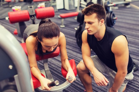 hamstrings: sport, fitness, lifestyle and people concept - young woman and personal trainer flexing leg muscles on gym machine