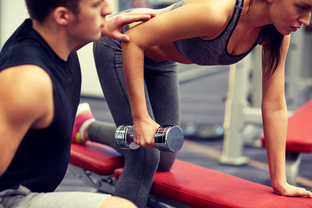 strength training: fitness, sport, exercising and weightlifting concept - close up of young woman and personal trainer with dumbbells flexing muscles in gym