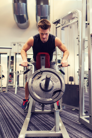 in a row: sport, bodybuilding, equipment and people concept - young man with barbell flexing muscles on t-bar row machine in gym Stock Photo