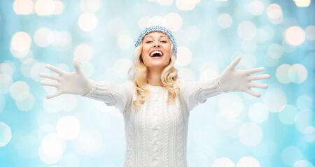 winter fashion: winter, fashion, christmas and people concept - smiling young woman in winter hat, sweater and gloves over blue holidays lights background