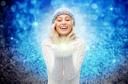 christmas light: winter, magic, christmas and people concept - smiling young woman in hat and sweater holding fairy dust on her palms over blue glitter or lights background