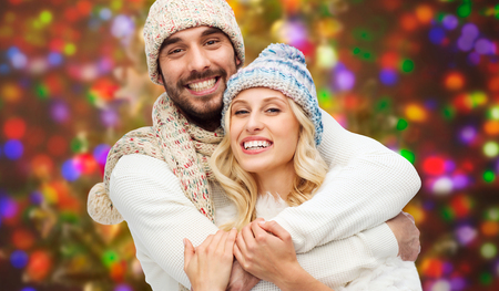 cuddling: winter, fashion, couple, christmas and people concept - smiling man and woman in hats and scarf hugging over holidays lights background