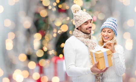 winter, holidays, couple, christmas and people concept - smiling man and woman in hats and scarf with gift box over lights background Foto de archivo