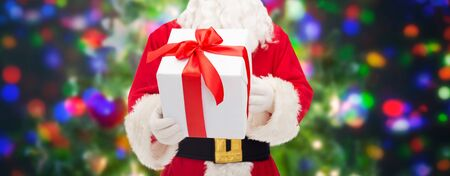 saint nick: christmas, holidays and people concept - close up of santa claus with gift box over lights background Stock Photo