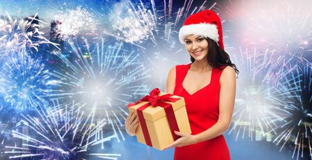 party night: people, holidays, christmas, new year party and celebration concept - beautiful sexy woman in red dress and santa hat with gift box over night city and firework background Stock Photo