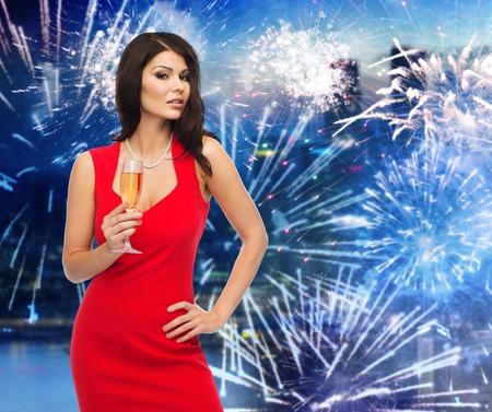 sektglas: Menschen, Urlaub, Weihnachten, Neujahr Party und Feier-Konzept - schöne sexy Frau im roten Kleid mit Champagner-Glas über Nacht Stadt und Feuerwerk Hintergrund