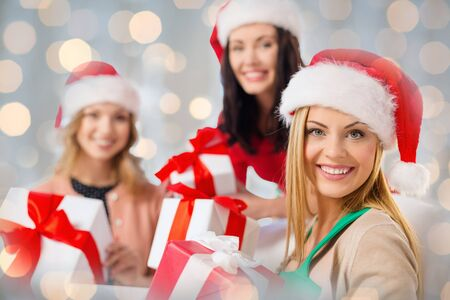 christmas present: christmas, winter, holidays and people concept - happy women in santa hats with gift boxes over lights background Stock Photo