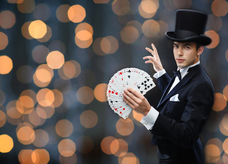 illusions: magic, gambling, casino, people and show concept - magician in top hat showing trick with playing cards over nigh lights background