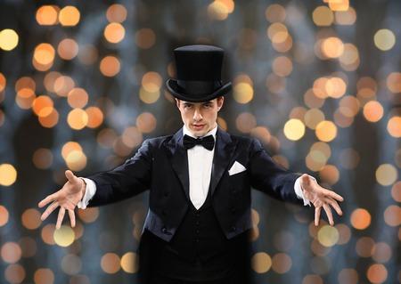 마술, 성능, 서커스, 사람들과 쇼 개념 - 마술사 모자 조명 배경 근처에 간 계를 게재