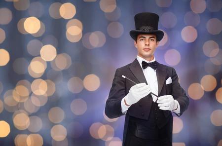 mago: el rendimiento, el circo, las personas y concepto de espect�culo - mago en el sombrero de copa con la varita m�gica sobre fondo luces cerca