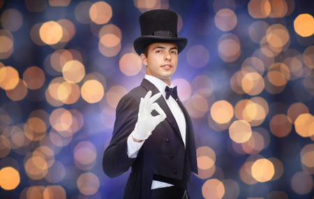 conjuring: magic, performance, circus, people and show concept - magician in top hat showing ok hand sign over nigh lights background Stock Photo