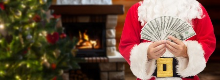 christmas profits: christmas, holidays, winning, currency and people concept - close up of santa claus with dollar money over living room with fireplace and christmas tree background