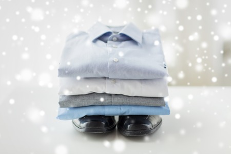 ironed: business, style, clothes, housekeeping and objects concept - close up of ironed and folded shirts and formal shoes on table at home over snow effect