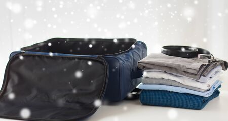clothes winter: business trip, luggage and clothing concept - close up of travel bag, shirts, trousers and belt over snow effect over snow effect