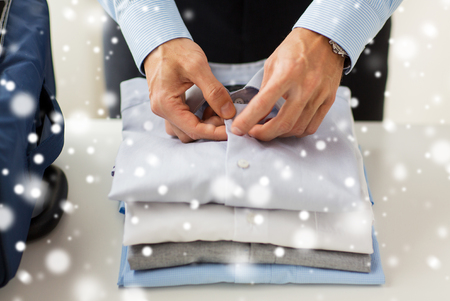trip over: business, trip, luggage and people concept - close up of businessman packing clothes into travel bag over snow effect