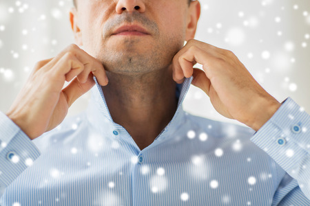 formal dressing: people, business, fashion and clothing concept - close up of man dressing up and adjusting shirt collar at home over snow effect