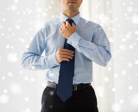 formal dressing: people, business, fashion and clothing concept - close up of man in shirt dressing up and adjusting tie on neck at home over snow effect